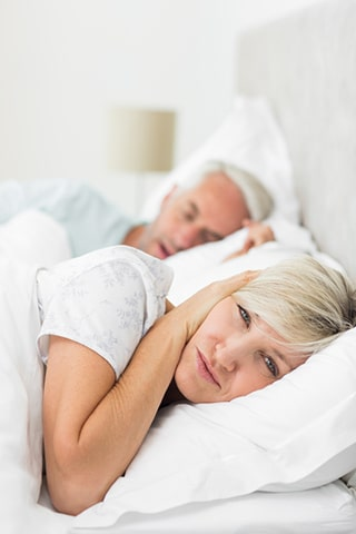 Wife covering ears due to snoring husband