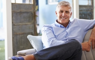 Portrait Of Smiling Mature Man Sitting On Sofa At Home