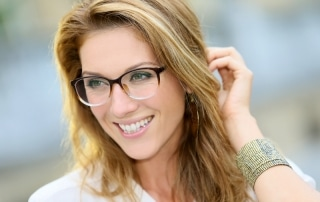 Young woman with glasses smiling and touching her hair