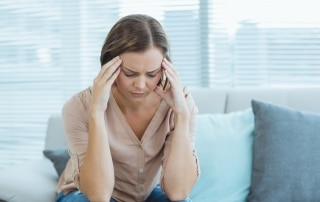 Woman sitting on a couch and holding her head in pain