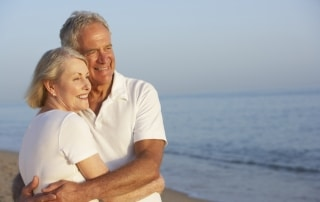 Older couple hugging on the beach
