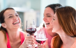 Three woman laughing and drinking wine