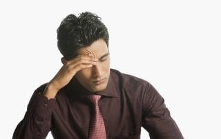 Man in a tie and nice shirt sitting with his hand on his head from migraine pain