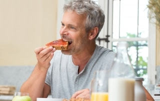 Mature man eating a piece of toast with strawberry jelly at his kitchen table