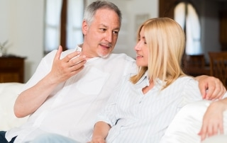 Happy mature couple talking in their home