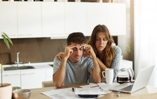A couple looking worried as they look at their bills