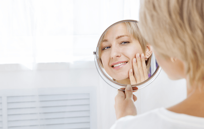 A woman looking at herself in a mirror after going to the dentist
