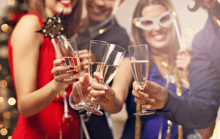 Group of four clinking champagne glasses at a dress up party