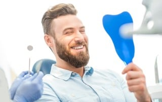 Man sitting in a dental chair, holding a mirror to look at his smile