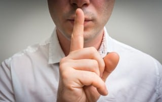A man holding is finger to his mouth to symbolize silence