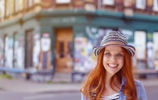 Smiling woman wearing a hat in the street