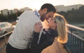 Man dipping a woman back while they both smile on a bridge