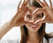 Beautiful Happy Woman Showing Love Sign Near Eyes