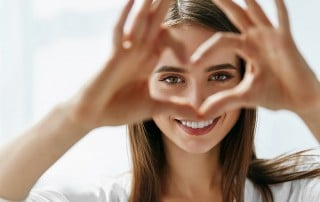 Beautiful Happy Woman Showing Love Sign Near Eyes