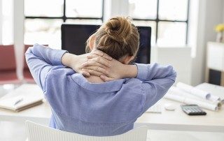 Woman sitting on couch with pain in her neck muscles.