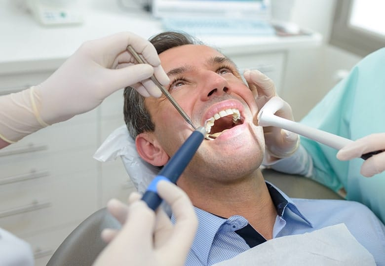 Middle aged man having dental treatment. After learning the negative impacts or silver & mercury dental fillings he's weighing his options at the Durham office