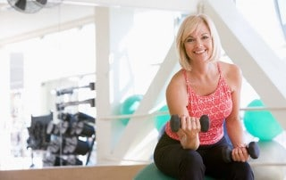 A woman using hand weights while sitting on a swiss ball at the gym. If you lose weight and are worried it could negatively impact your face, look at a Non-surgical facelift.