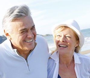 Older couple laughing on the beach with beautiful teeth