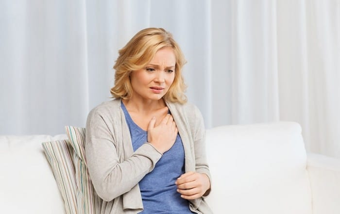 Woman resting on her couch experiencing a heart attack. While rare, women experience jaw pain as one of their heart attack symptoms. In this case, the pain will come on suddenly, and may persist for several minutes. It may be accompanied by shortness of breath, a cold sweat, nausea or lightheadedness.