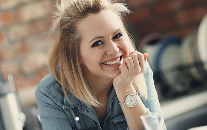 Beautiful blonde haired woman relaxing at home while smiling, resting her hand on her chin. If you are considering a smile makeover, you want to make sure that the results look good.