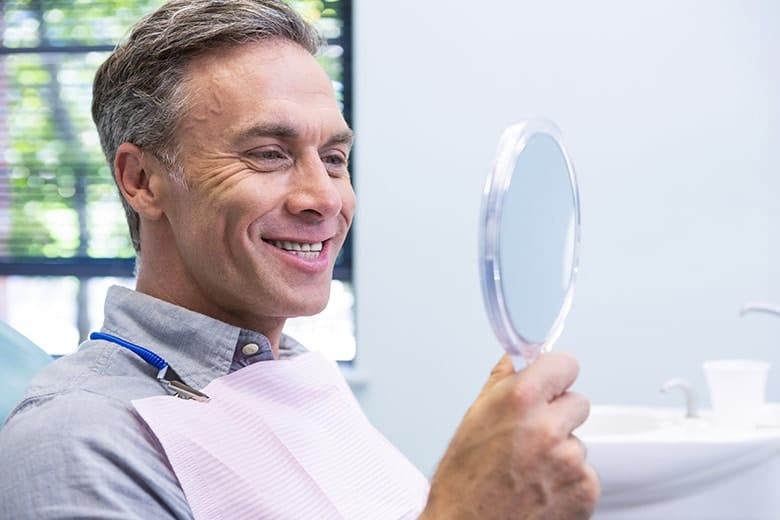 A attractive middleaged man with a white smile with no more metal fillings. At The Durham Office, We pioneered the move away from metal restorations, becoming a strong, early advocate for the use of more attractive and biocompatible materials, and we honor that legacy today by helping people enjoy beautiful, healthy, metal-free restorations whenever possible.
