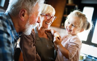 Retired couple enjoy a laugh with their granddaughter