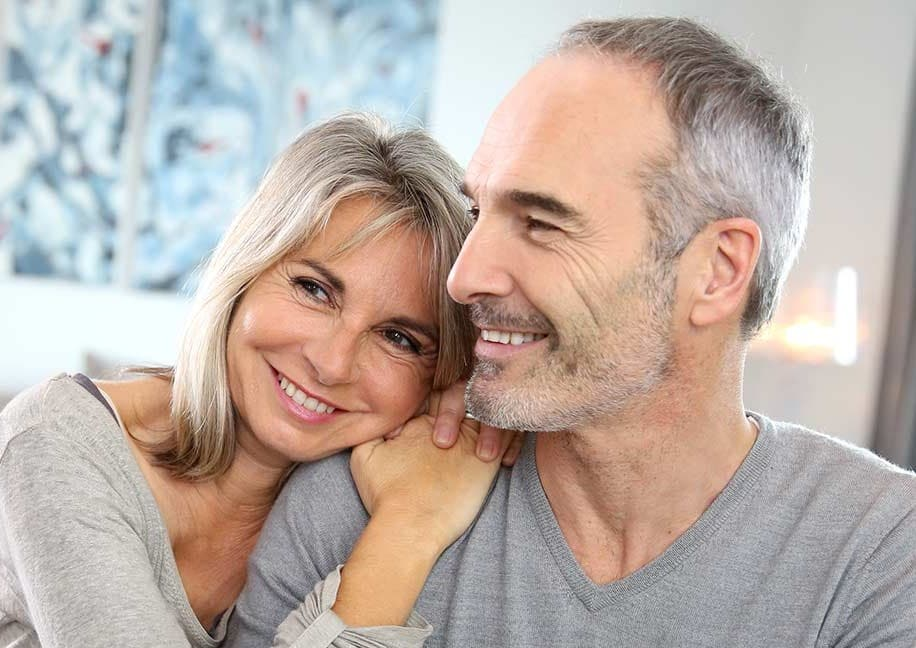Happy middle aged couple enjoys each other's company at home