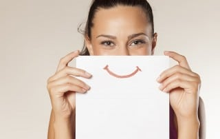 woman holding a piece a paper with a smile on it in front of her face