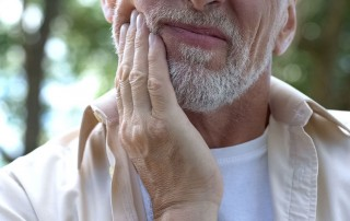 older man massaging his jaw due to pain